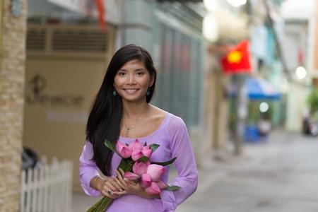 ao: Vietnamese woman holding lotus flowers bud bunch Stock Photo