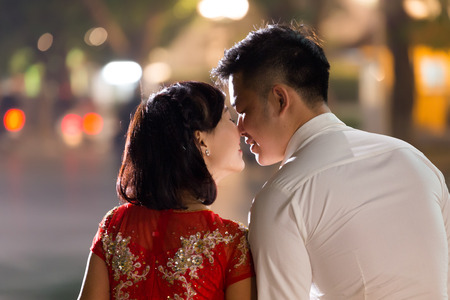 HANOI, VIETNAM, DECEMBER 15, 2014: Two young married people are exchanging a love kiss in evening at the city center's Hoan Kiem lake in Hanoi city, Vietnam. Imagens - 38459110