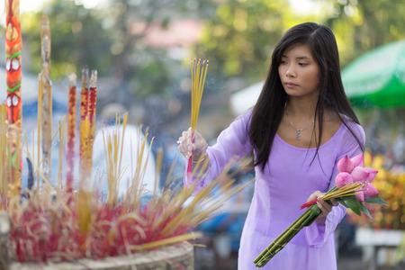 Vietnamese woman inserting incense stick in giant burner praying at temple photo