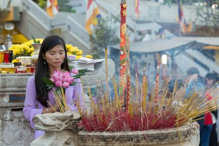 Asian Buddhist woman praying in temple, holding lotus flower buds bunch, Vietnam photo
