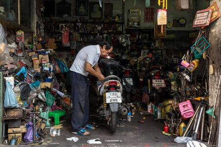 messy house: BANGKOK, THAILAND, JANUARY 15, 2015: A man is repairing a motorbike inside his modest garage shop in the Chinatown district of Bangkok, Thailand.