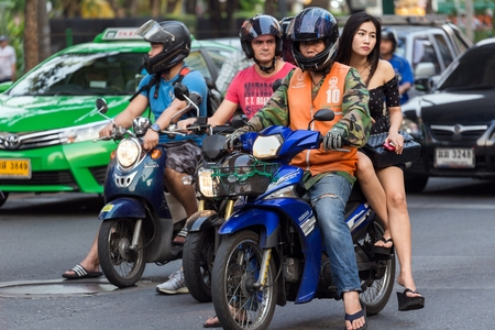 mototaxi: BANGKOK, THAILAND, February 15, 2015: A moto taxi is carrying a young Thai lady on his motorbike in the Sukhumvit road near the Thong Lor BTS station in Bangkok, Thailand