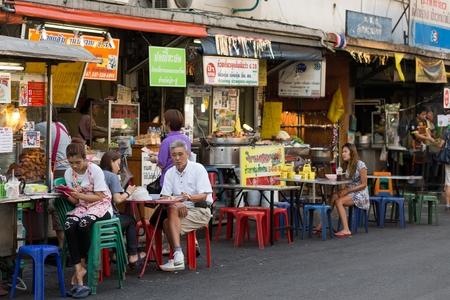 一部の顧客がスクンビットのソイ 38、トンロア地区バンコク、タイの屋台の食べ物の有名な場所でレストランのテーブルに座っているバンコク、タ
