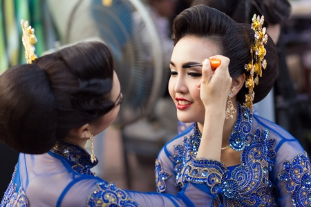 BANGKOK, THAILAND, February 17, 2015: A Thai lady traditonal dancer is applying make up on eyebrows friend before the show celebrating the new Krung Kasem floating market in the Thewet district of Bangkok, Thailand
