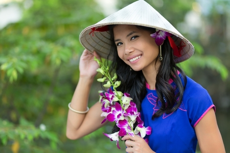 conical hat: Pretty Vietnamese woman wearing a traditional conical hat holding orchid flower bunch