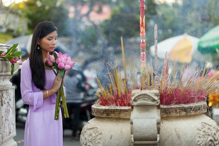 Vietnamese Buddhist woman praying in temple, holding lotus flower buds bunch, Vietnam
