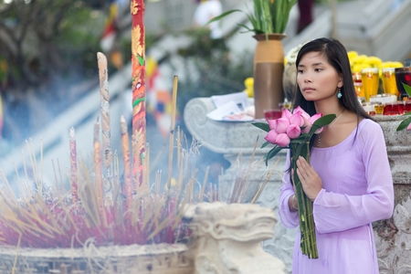 Buddhist woman praying in temple, holding lotus flower buds bunch, Vietnam