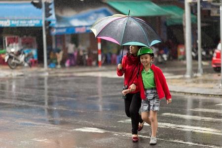 Da Nang, Vietnam, 14 de diciembre 2015: Una mujer vietnamita y su hijo están cruzando una calle bajo una lluvia tropical en Da Nang, Vietnam