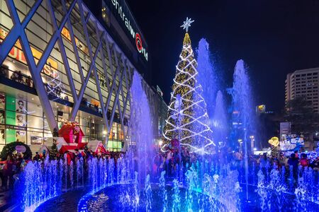 BANGKOK, THAILAND, DECEMBER 25, 2014: Colorful fountain and huge Christmas tree on the Central World square in front of the mall in Bangkok, Thailand
