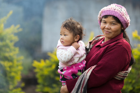 south asian ethnicity: MAE KLANG LUANG, THAILAND, DECEMBER 31, 2014: A friendly Karen tribe woman in traditional clothes is holding her kid in the village of Mae Klang Luang in the Doi Inthanon national park near Chiang Mai, Thailand Editorial
