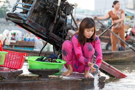 en cuclillas: Can Tho, Vietnam, 12 de diciembre 2014: Una mujer está lavando la ropa a bordo de un barco comercial en el mercado flotante de Cai Rang en el río Mekong, en la ciudad de Can Tho, Vietnam.