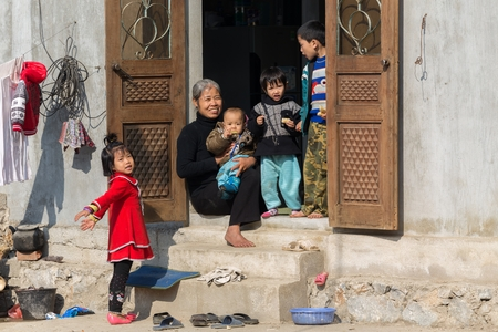 MAI CHAU, VIETNAM, DECEMBER 12, 2014: A happy Chinese grandmother and her grandchildren are enjoying the sunlight at the home entrance in the village of Mai Chau, Vietnam