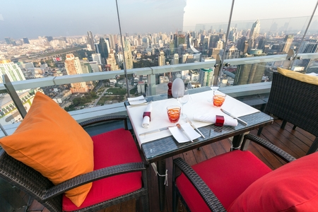 bar top: BANGKOK, THAILAND, JANUARY 14, 2015: Restaurant table with view on the cityscape at the Red Sky Rooftop of the Centara hotel in Bangkok, Thailand.
