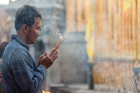 burning man: LAMPHUN, THAILAND, DECEMBER 31, 2014: A man holding burning incense sticks is praying for the new year outside the Buddhist temple of Wat Phra That Hariphunchai in Lamphun, Thailand
