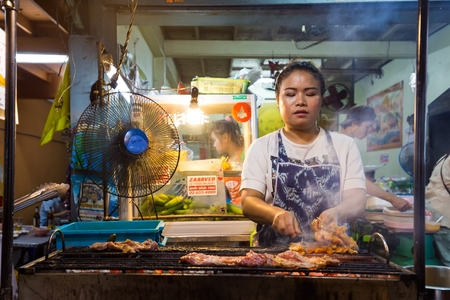 38: BANGKOK,THAILAND,FEBRUARY 16,2015: A woman is cooking chicken brochettes on barbecue in a small restaurant of the Sukhumvit Soi 38 in Bangkok,Thailand