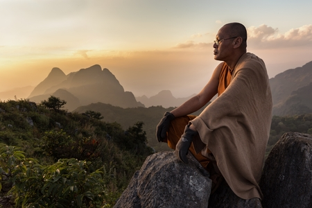 master: CHIANG DAO, THAILAND, JANUARY 05, 2015: A Buddhist monk master is meditating at the top of the Chiang Dao mount at dusk for the new year in Thailand.