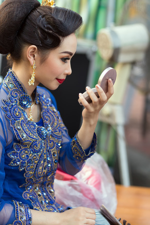 krung: BANGKOK, THAILAND, February 17, 2015: A Thai lady traditional dancer is checking her makeup make up on a mirror before the show celebrating the new Krung Kasem floating market in the Thewet district of Bangkok, Thailand