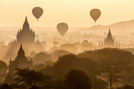 Air balloons flying over pagodas at misty dawn in the plain of Bagan Myanmar Burma