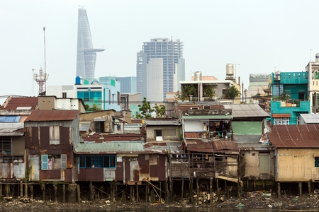 Poor shanti Saigon wooden house on the river bank in front of modern buildings in Ho Chi Minh city Vietnam Editorial