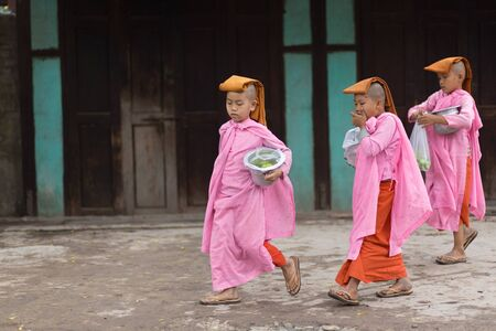 nuns: MANDALAYMYANMARJANUARY 17 2015: A group of young Buddhist nuns is walking in the streets of Mandalay Myanmar Burma.