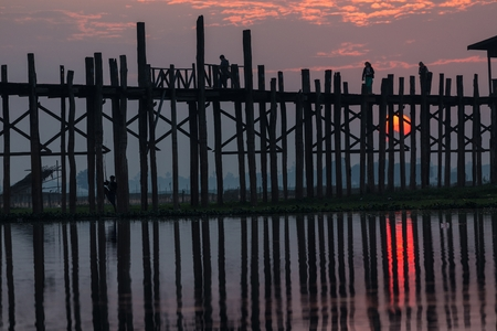 teck: U bein wooden teck bridge with red sunset behind the structure, Amarapura, Myanmar (Burma) Stock Photo