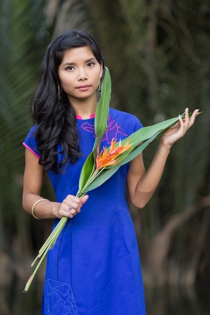 non la: Young pretty Vietnamese woman in blue Ao Dai dress holding orange flowers with big leaves, looking the camera.