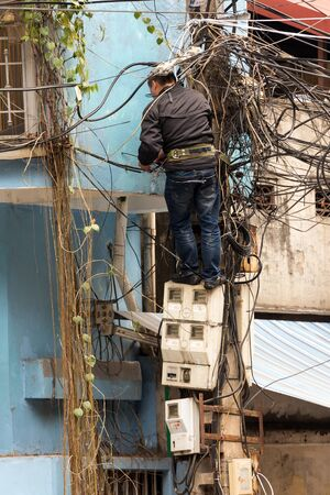 lineman: HANOI, VIETNAM, DECEMBER 16, 2014 : A technician standing on the electricity meters is repairing or checking the messy electrical network in the city of Hanoi, Vietnam Editorial