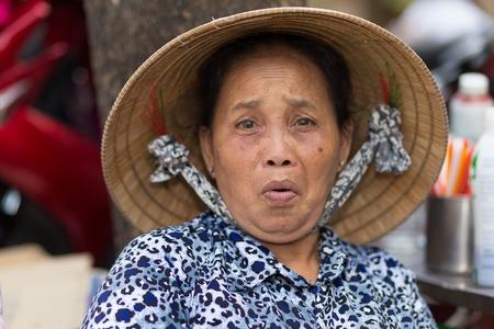 vietnamese ethnicity: SAIGON, VIETNAM, FEBRUARY 26, 2015 : A funny senior woman is making a grimace in the streets of Saigon (Ho Chi Minh), Vietnam Editorial