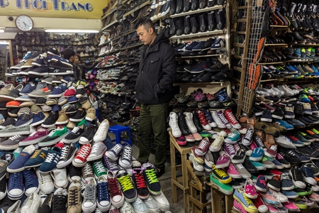 HANOI, VIETNAM, DECEMBER 15, 2014 : An undecided man is taking a look in a shop specialized in the selling of shoes in Hanoi, Vietnam Editorial