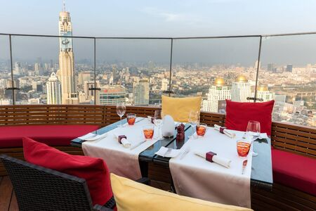 red sky: BANGKOK, THAILAND, JANUARY 14, 2015: Restaurant table with view on the Baiyoke tower and cityscape at the Red Sky Rooftop of the Centara hotel in Bangkok, Thailand. Editorial