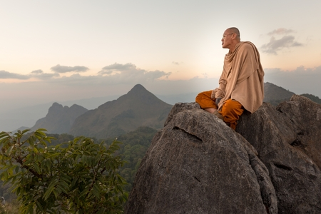 meditation man: CHIANG DAO, THAILAND, JANUARY 05, 2015: A Buddhist monk master is meditating at the top of the Chiang Dao mount at dusk for the new year in Thailand.