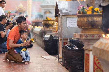 hariphunchai: LAMPHUN, THAILAND, DECEMBER 31, 2014: A man and his son are praying for the new year outside the Buddhist temple of Wat Phra That Hariphunchai in Lamphun, Thailand