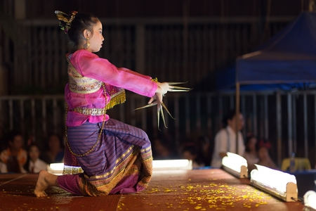 thai dancing: CHIANG MAI, THAILAND, JANUARY 04, 2015: A woman is performing a Thai traditional dance at an outdoor stage during the Saturday night street market in Chiang Mai, Thailand Editorial