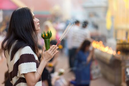 buddhism prayer belief: LAMPHUN, THAILAND, DECEMBER 31, 2014: A woman holding burning incense sticks and flowers is praying for the new year outside the Buddhist temple of Wat Phra That Hariphunchai in Lamphun, Thailand Editorial