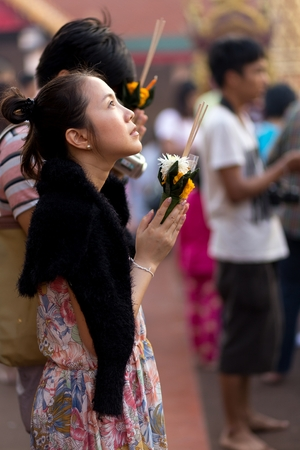 hariphunchai: LAMPHUN, THAILAND, DECEMBER 31, 2014: A woman holding burning incense sticks and flowers is praying for the new year outside the Buddhist temple of Wat Phra That Hariphunchai in Lamphun, Thailand Editorial