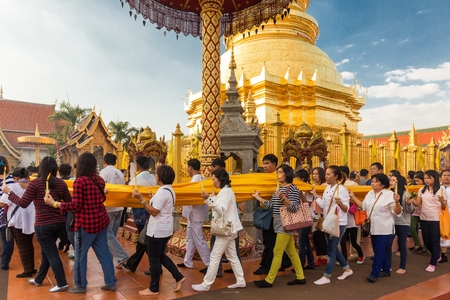 hariphunchai: LAMPHUN, THAILAND, DECEMBER 31, 2014: Thai people are holding a long sacred cloth, in procession around the Wat Phra That Hariphunchai temple for celebrating the new year in Lamphun, Thailand Editorial