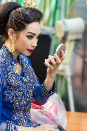 krung: BANGKOK, THAILAND, February 17, 2015 : A Thai lady traditional dancer is checking her makeup before the show celebrating the new Krung Kasem floating market in the Thewet district of Bangkok, Thailand