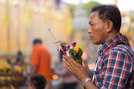 incienso: Lamphun, Tailandia, 31 de Diciembre, 2014: Un hombre que sostiene la quema varitas de incienso y flores de orquídeas es orar por el Año Nuevo fuera del templo budista de Wat Phra que Hariphunchai en Lamphun, Tailandia