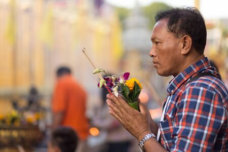 hariphunchai: LAMPHUN, THAILAND, DECEMBER 31, 2014: A man holding burning incense sticks and orchid flowers is praying for the new year outside the Buddhist temple of Wat Phra That Hariphunchai in Lamphun, Thailand