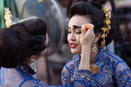 make up artist: BANGKOK, THAILAND, February 17, 2015: A Thai lady traditional dancer is applying make up on eyebrows friend before the show celebrating the new Krung Kasem floating market in Bangkok, Thailand