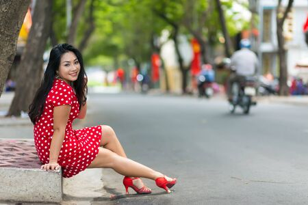 red dress: HO CHI MINH CITY, VIETNAM, FEBRUARY 22, 2015: A Vietnamese woman in glamorous vivid red dress is posing in the street, sitting on the sidewalk border in Ho Chi Minh City, Saigon, Vietnam. Editorial