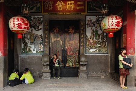 disctrict: HO CHI MINH CITY, VIETNAM, FEBRUARY 24, 2015: Their Parents Kids after school waiting at the entrance of the Ong Bon Pagoda in Chinatown, 5 disctrict of Ho Chi Minh City, Saigon, Vietnam.