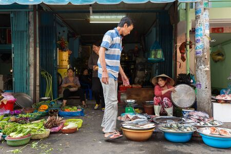 tay: HO CHI MINH CITY, VIETNAM, FEBRUARY 26, 2015: A family is selling vegetables and fishes in the street at the Cho Binh Tay market in the Chinatown district of Ho Chi Minh City, Saigon, Vietnam.