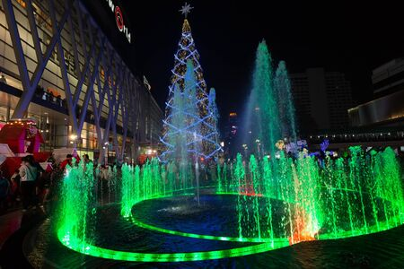 huge christmas tree: BANGKOK, THAILAND, DECEMBER 25, 2014: Colorful fountain and huge Christmas tree on the Central World square in front of the mall in Bangkok, Thailand