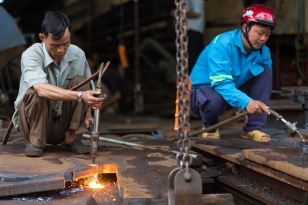 CAN THO, VIETNAM, DECEMBER 11, 2014 : Two men are welding a metallic structure without any protection in the market of Tan An in Can Tho, Vietnam