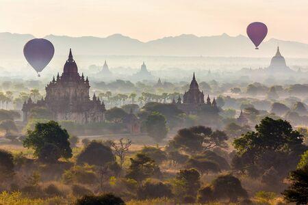 mist: Air balloons flying over pagodas at misty dawn in the plain of Bagan, Myanmar (Burma)