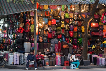 sidewalk sale: HANOI, VIETNAM, DECEMBER 16, 2014 : A couple is selling a very large choice of bags and suitcases in the streets of Hanoi, Vietnam