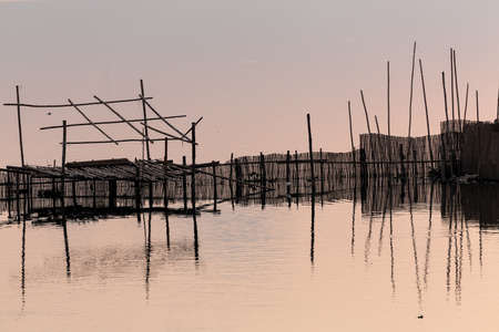 silhouetted: Wooden fishing fence and structure silhouetted at dusk on the lake Taungthaman in Amamapura, Myanmar Stock Photo