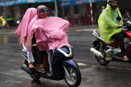 rain wet: DA NANG, VIETNAM, DECEMBER 14, 2015: Vietnamese people riding motorbike under a heavy rain, full covered with raincoat in Da nang, Vietnam
