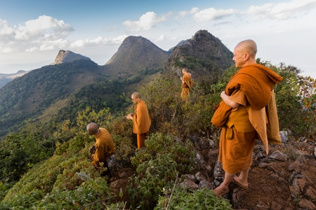 mount: CHIANG DAO, THAILAND, JANUARY 05, 2015: A group of Buddhist monks is standing at the top of the Chiang Dao mount at dusk for the new year in Thailand.